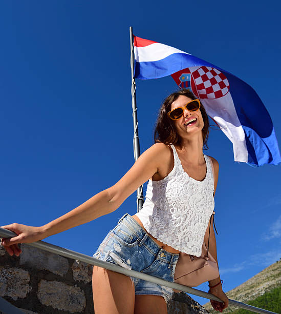 Young woman tourist Dubrovnik, wall, and flag in background - foto de acervo
