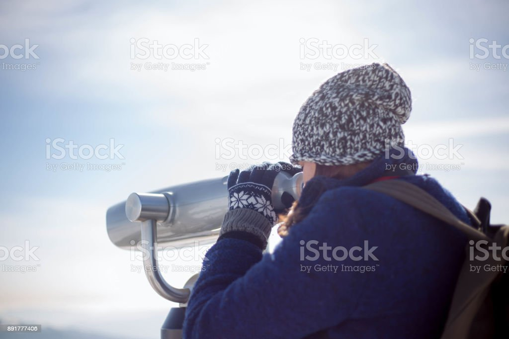 Young woman tourist looking through binoculars in winter in snowy weather stock photo