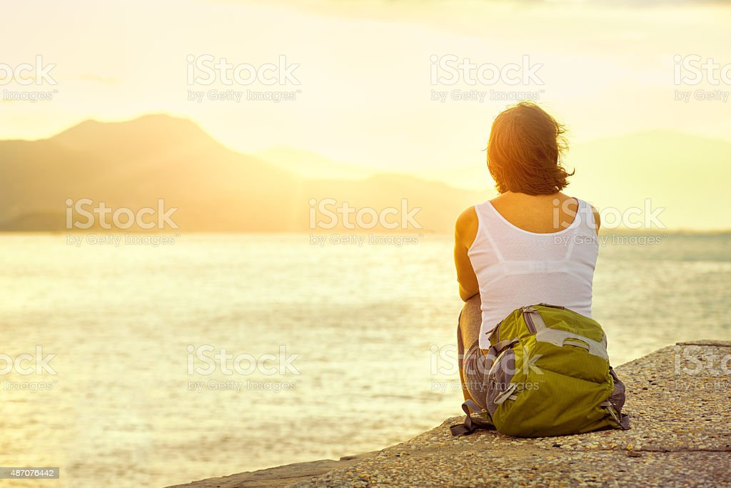 Young woman tourist  sit pier looking sunset on the island stock photo