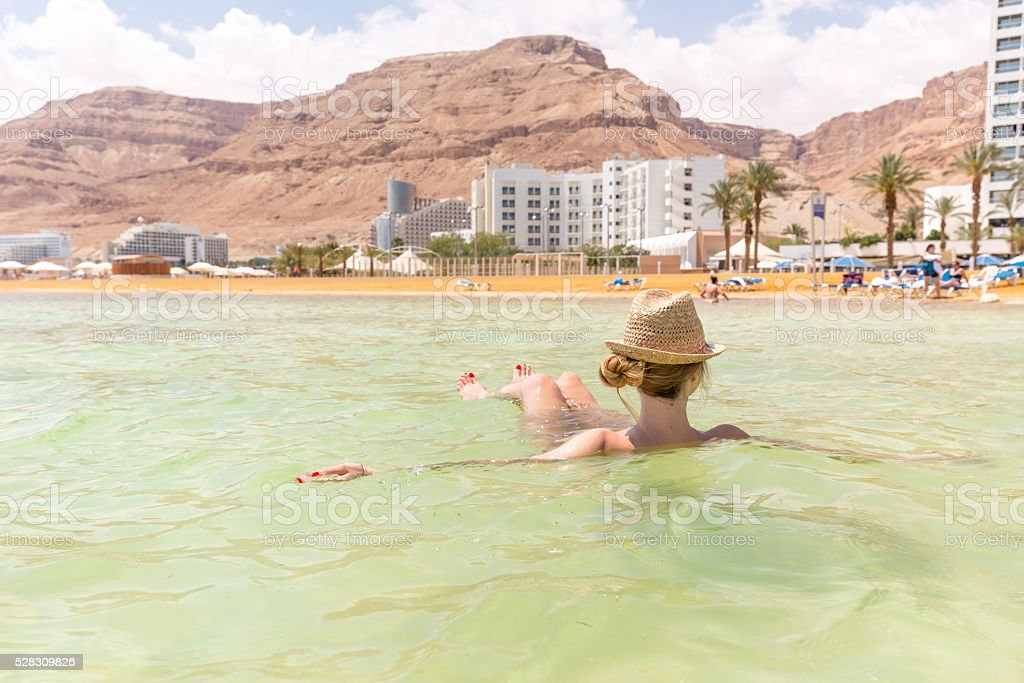 Young woman tourist swimming floating salty water, Dead sea. stock photo