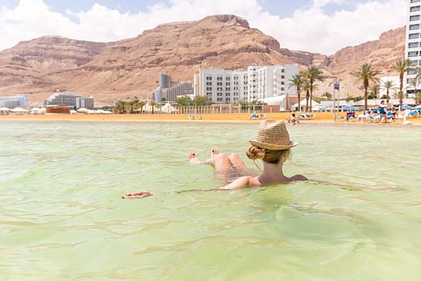 młoda kobieta pływające w wodzie, słonymi turystów pływać, martwe sea. - morze martwe zdjęcia i obrazy z banku zdjęć