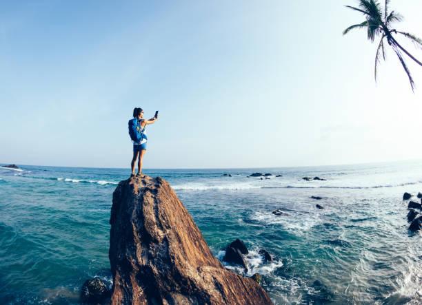 Junge Touristin fotografiert am Felsrand am Meer – Foto
