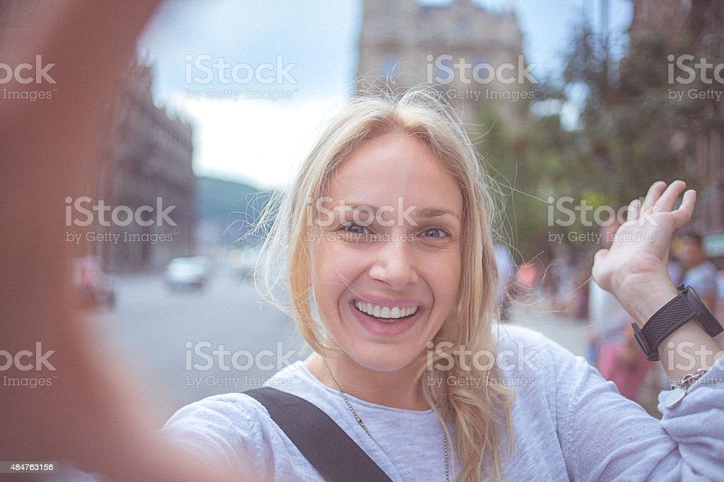 Young woman tourist taking selfie in the city - POV stock photo