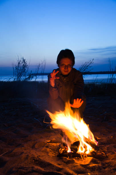 young woman tourist warms hands at night campfire on the beach stock photo
