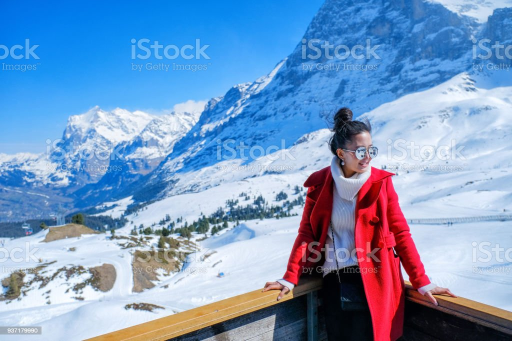 Young Woman Tourists see beautiful viewpoitn near Kleine Scheidegg station, along the railway from Interlaken to Jungfraujoch (3,466 m). In daylight atI Switzerland stock photo