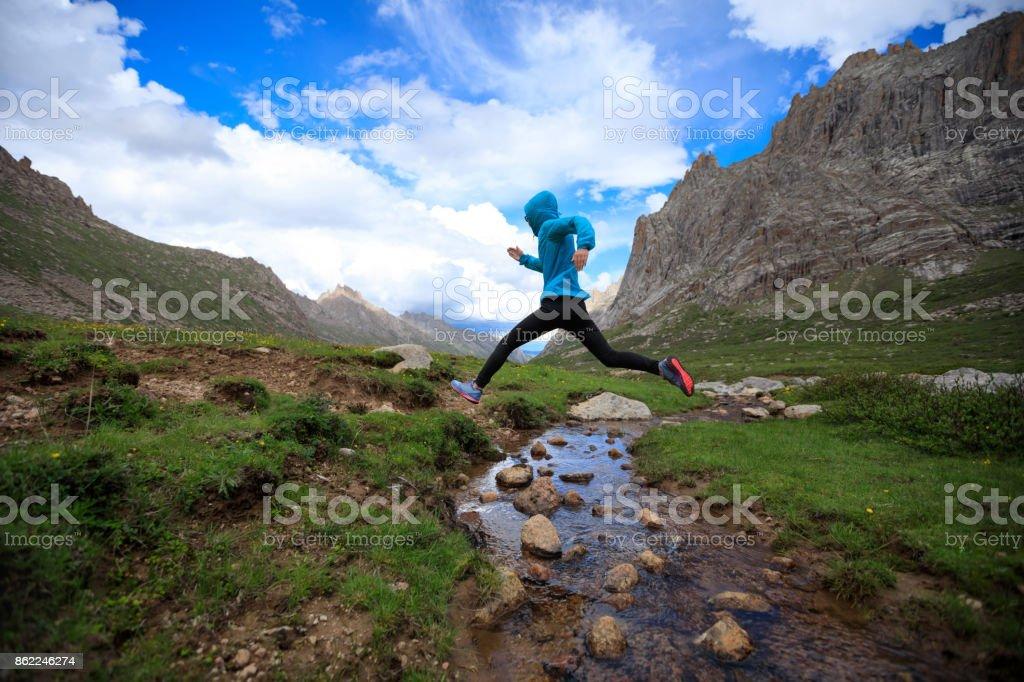 junge Frau Trailläufer springen über Bachwasser am Berg – Foto