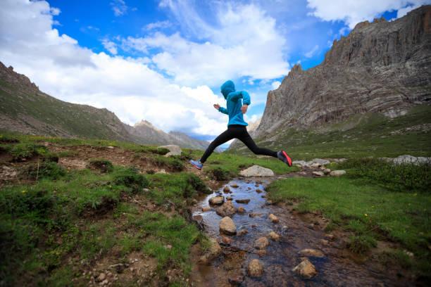 corredor de trail de mujer joven saltando sobre el agua corriente en la montaña - trail running fotografías e imágenes de stock