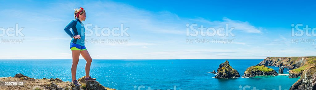 Young woman trail runner looking over blue ocean coast panorama stock photo