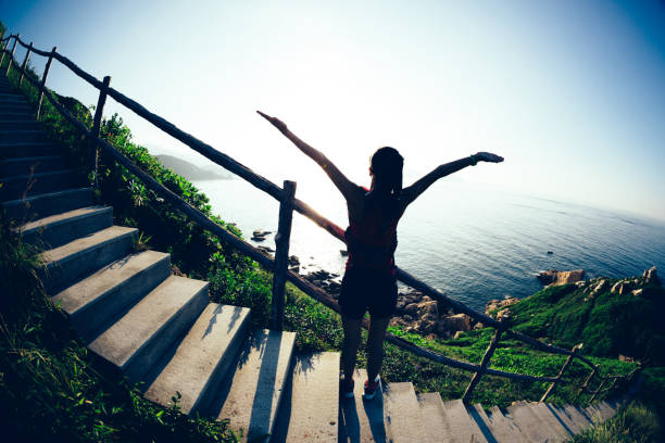 Young woman trail runner open arms on sunrise seaside Young woman trail runner open arms on sunrise seaside real life stock pictures, royalty-free photos & images