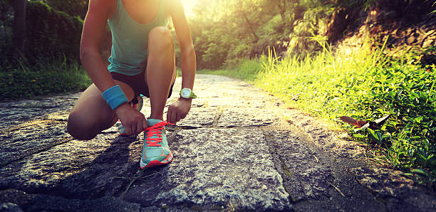 young woman trail runner tying shoelaces in forest - foto de stock
