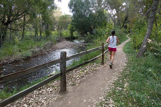 Following the path of the river, a woman runs down a winding trail along Bear Creek, Colorado.