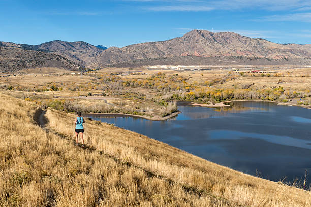 During a bright fall morning in the grasslands of Bear Creek Lake Park, a young woman with a pony tail runs through the tall golden grasses past the lake towards Mount Morrison and Red Rocks Park and Ampitheater in the the distance, Morrison, Colorado