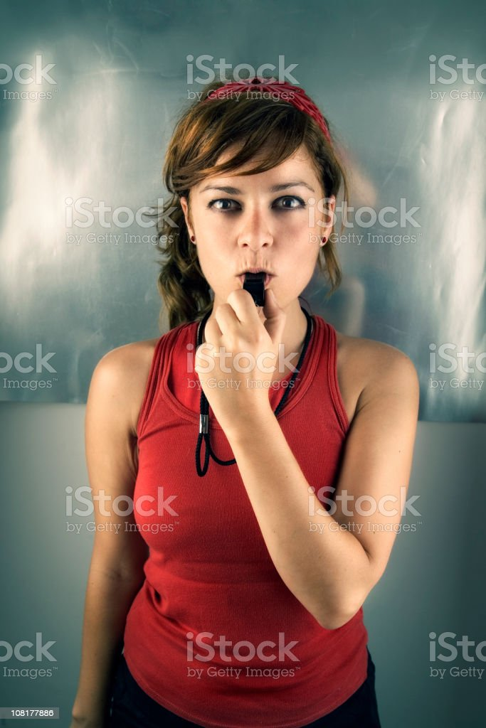 Young Woman Trainer Blowing Whistle royalty-free stock photo