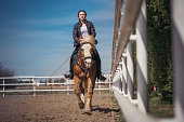 Young woman trainer riding a beautiful horse