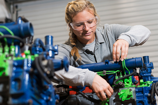 A young woman in vocational school learning the auto mechanic trade.  She is working on a diesel engine that has been color-coded for educational use.