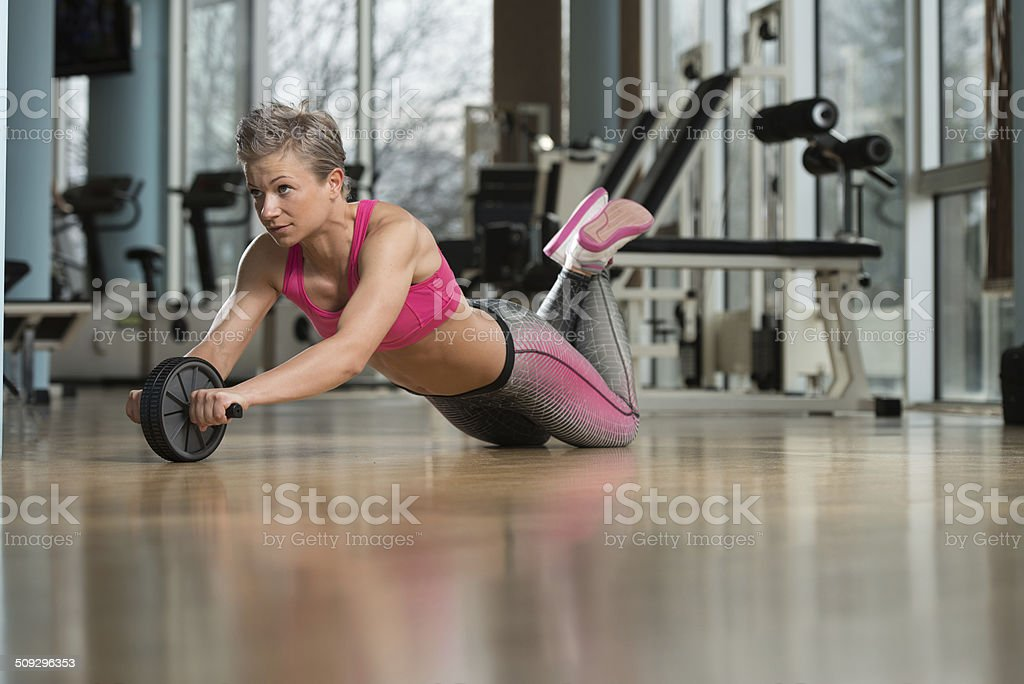 Young Woman Training With Ab Wheel stock photo