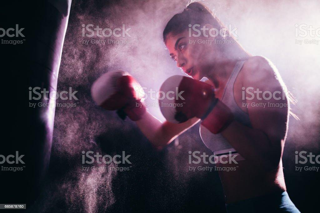 Mujer joven con guantes de boxeo y un saco de boxeo - foto de stock