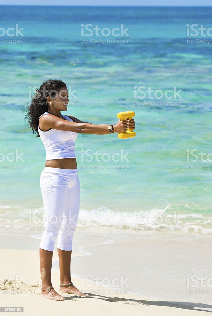 Young woman training with dumbells on a tropical turquoise beach royalty-free stock photo
