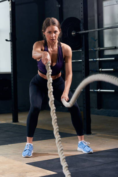 Young Woman Training with Ropes in gym Gym stock photo