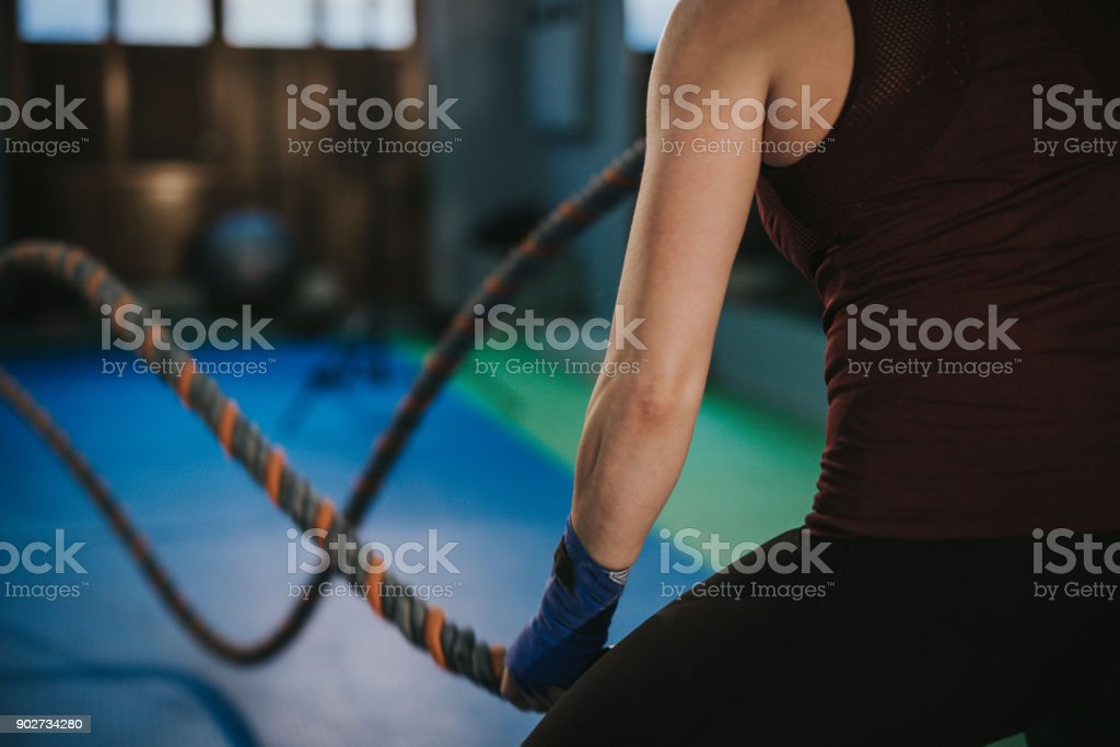 Young Woman Training with Ropes in Gym stock photo