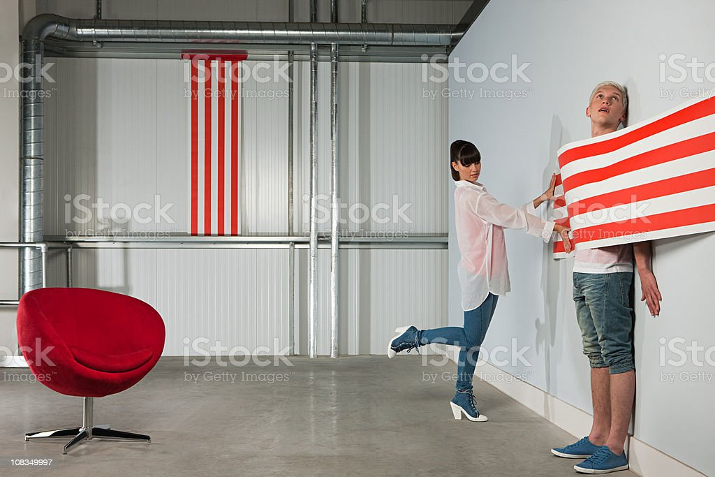 Young woman trapping young man behind striped wallpaper stock photo