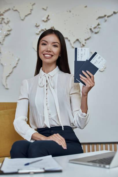 mujer joven agente de viajes con billetes de avión en manos - agente de viajes fotografías e imágenes de stock