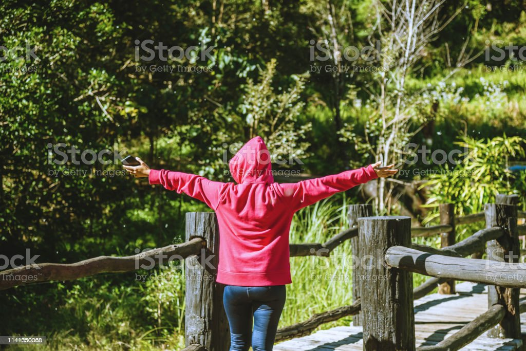 Young woman travel nature is walking forward in the direction of the wooden bridge. Young woman travel nature is walking forward in the direction of the wooden bridge. Active Lifestyle Stock Photo