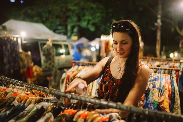 jonge vrouw reiziger browsen via de winkels in bangkok street markt - avondmarkt stockfoto's en -beelden