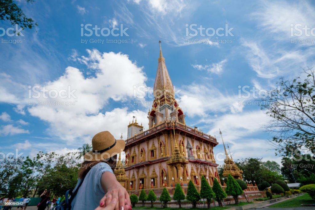Ung kvinna traveler hålla handen man in vackra pagoden i Wat Chalong eller Chalong-templet på Phuket town, Thailand. Det är mest populära thailändska templet i Phuket Thailand. - Royaltyfri Andlighet Bildbanksbilder