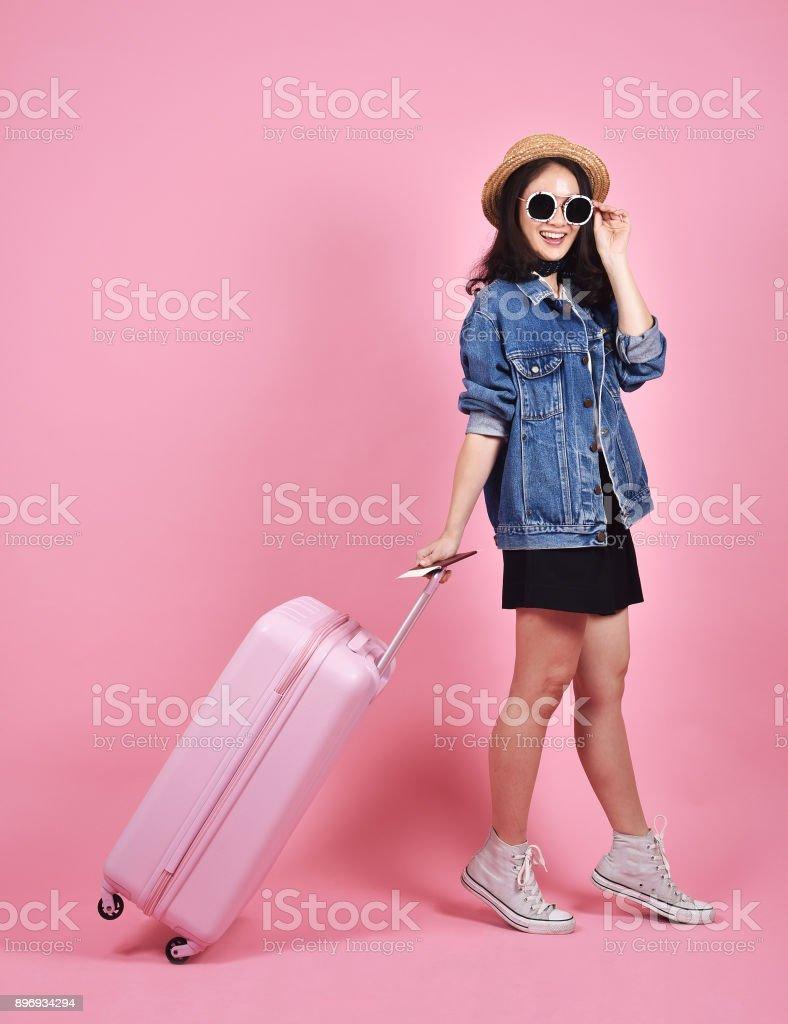 Junge Frau Reisenden halten rosa Koffer und Pass über rosa Hintergrund, Reise dokumentieren und Reise-Konzept. – Foto