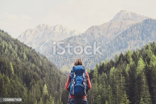 Young girl traveler on a walking route, active lifestyle, hiking and travel concept. Women looking at lake in winter