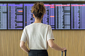 Young woman traveler looking at flight information