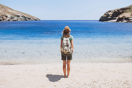 Young woman traveler looking at the sea, travel concept