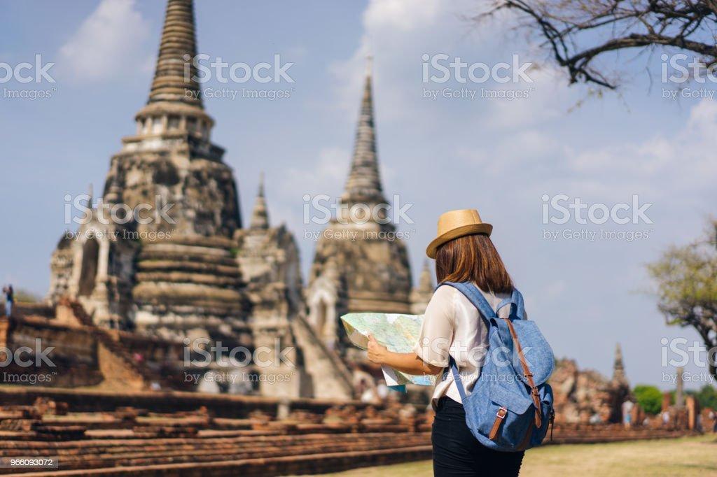 Ung kvinna traveler tittar Wat Phra Si Sanphet i Ayutthaya historiska park i Ayutthaya provinsen nära Bangkok Thailand karta med bakgrund av tre gamla pagoda. - Royaltyfri Andlighet Bildbanksbilder