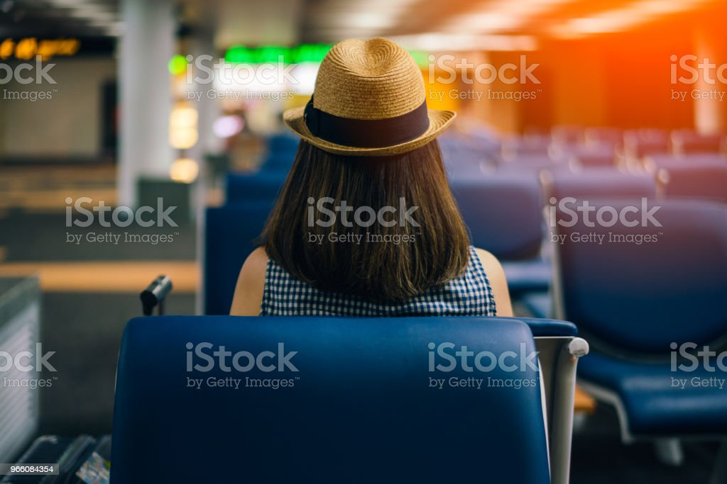Young woman traveler sitting on chair of passenger in an airport lounge waiting for flight aircraft - Стоковые фото Аэропорт роялти-фри