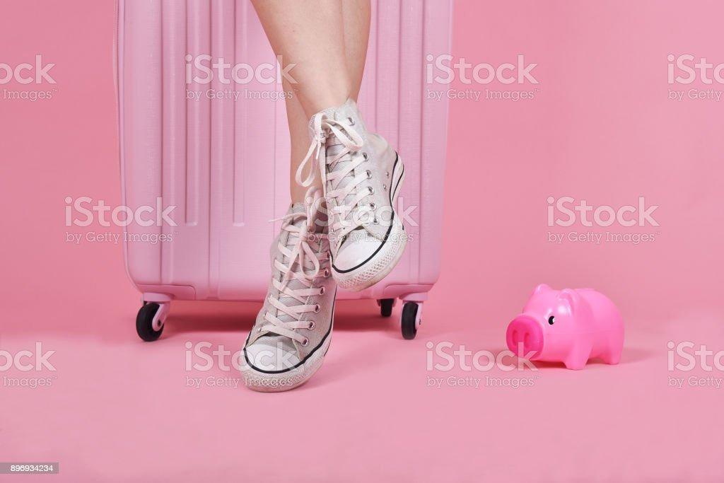 Junge Frau Reisende sitzen auf Koffer über rosa Hintergrund, Reise und Reisen Konzept. – Foto