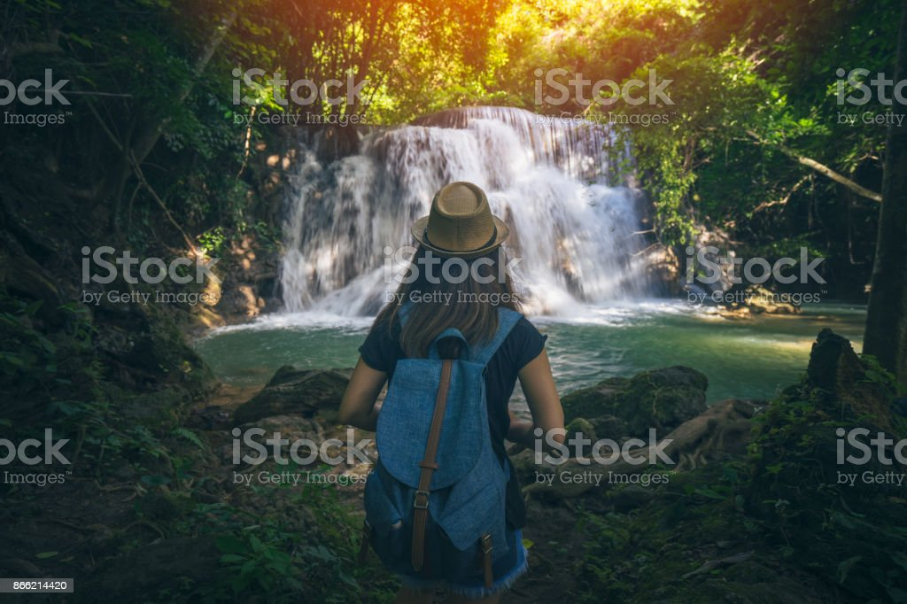 Young woman traveler travel into amazing beautiful waterfalls in tropical forest stock photo