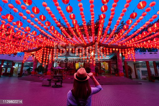 istock Young woman traveler traveling and looking red lanterns decorations in chinese temple 1129802214