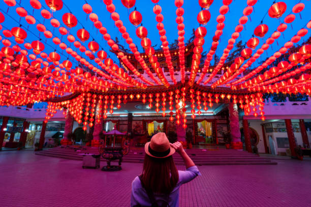 jonge vrouw reiziger reizen en op zoek naar rode lantaarns decoraties in de chinese tempel - maleisië stockfoto's en -beelden