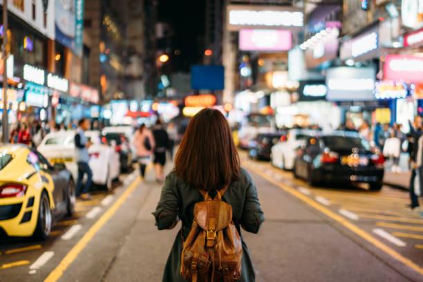 Young woman traveler traveling into Mongkok street market at night in Hong Kong China