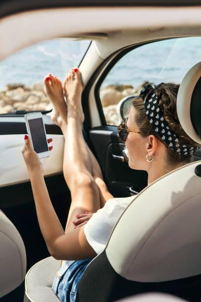 Junge Frau Reisenden über Telefon auf Auto – Foto
