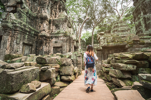 istock Young woman traveler visiting in ta prohm temple at Angkor Wat complex, Khmer architecture heritage in Siem Reap, Cambodia 1017593966