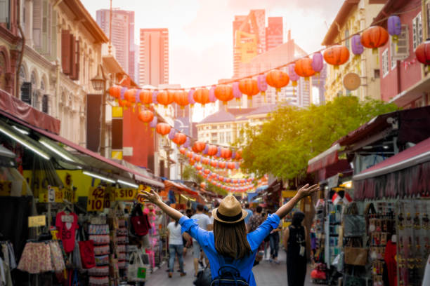 young woman traveler with backpack and hat traveling into chinatown at singapore city downtown. travelling in singapore concept - singapore stock photos and pictures