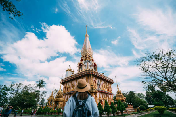 young woman traveler with backpack traveling into beautiful pagoda in wat chalong or chalong temple at phuket town, thailand. it's most popular thai temple in phuket thailand. - phuket stock photos and pictures