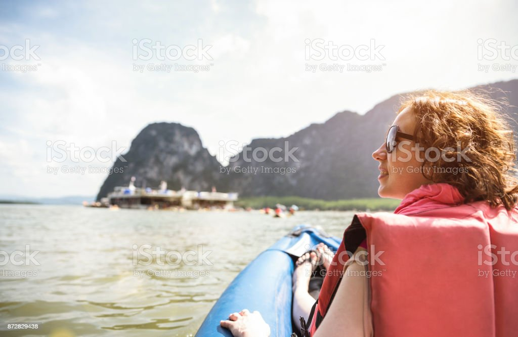 Young woman traveler with life jacket at sunset ride on kayak island hopping - Wanderlust travel concept with adventure girl tourist wanderer on excursion in Thailand - Warm vintage sunshine filter stock photo