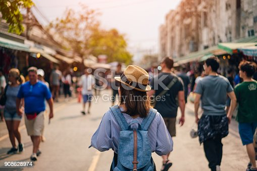 istock Young woman traveler with sky blue backpack and hat looking the way with in JJ Market in Bangkok Thailand. Traveling in Bangkok Thailand 908628974