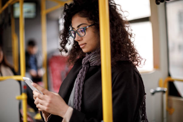 Young woman traveling by bus and using smart phone stock photo