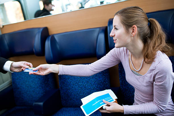 young woman traveling by train, having her ticket checked - transport conductor stock photos and pictures