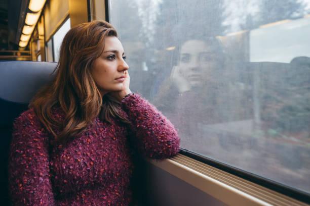 junge frau reisen in zug - in gedanken versunken - bahn bus stock-fotos und bilder