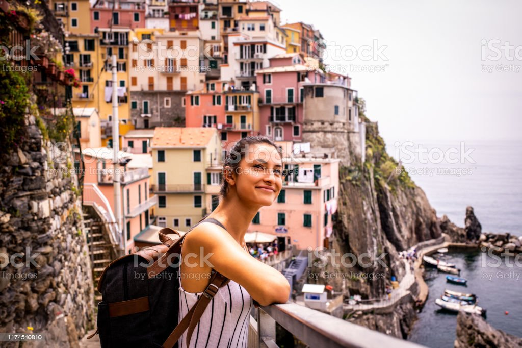 Young woman traveling Italy. Female tourist relaxing by the sea. She is looking at the beautiful town Riomaggiore, Cinque Terre Adult Stock Photo